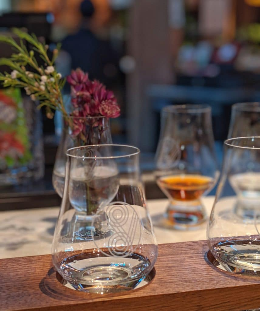 Image of tasting glasses with a vase of flowers in the background.