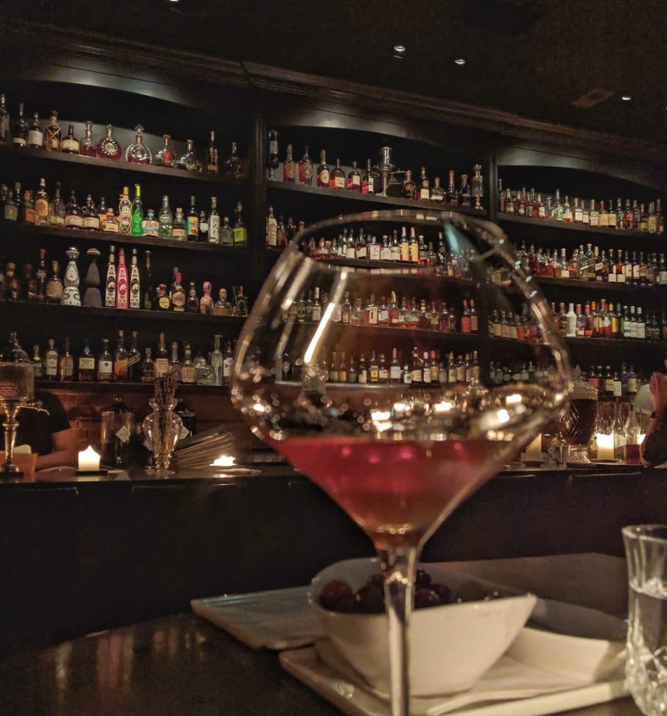 Picture of cocktail against bar with hundreds of bottles behind it.